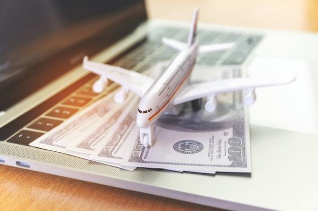 Ordenador portátil y avión y dinero en la mesa. concepto de reserva de entradas online