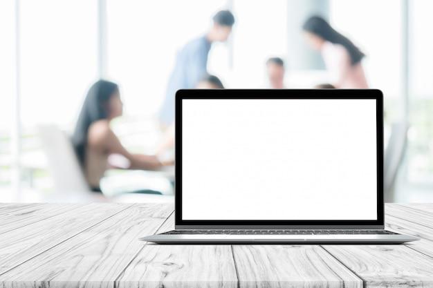 Ordenador portátil en blanco simulacro pantalla colocada en mesa de madera blanca en reunión de personas borrosa
