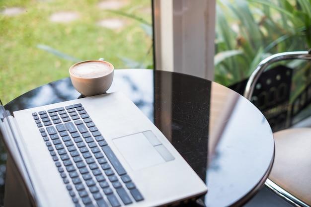 Ordenador portátil con café con leche caliente en taza blanca sobre mesa de cristal