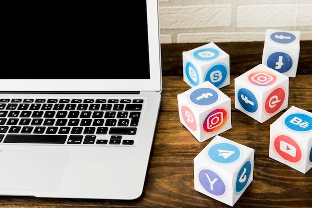 Ordenador portátil cerca de cajas de iconos de aplicaciones sociales en la mesa