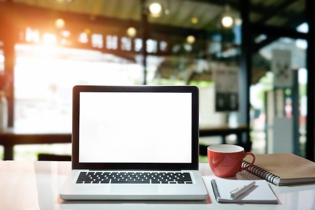 Ordenador portátil de la computadora de la oficina con el papel de la libreta, la pluma y la taza de café con la pantalla de visualización vacía.