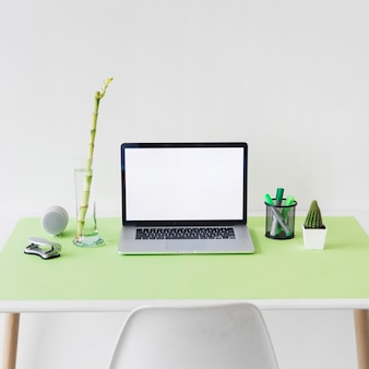 Ordenador portátil con pantalla blanca en blanco en el escritorio de oficina