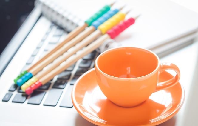 Ordenador portátil con taza de café y bloc de notas en el escritorio