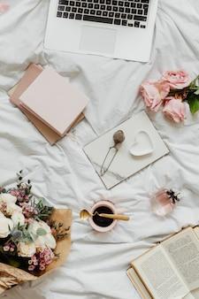 Ordenador portátil y cuadernos en la cama de una niña