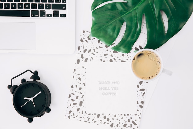 Ordenador portátil; despertador; hoja de monstruo; taza de café; notas adhesivas con mensaje y papel sobre escritorio blanco.