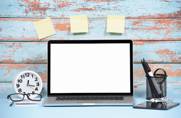 Ordenador portátil; despertador; tableta digital y notas adhesivas en blanco en pared de madera.