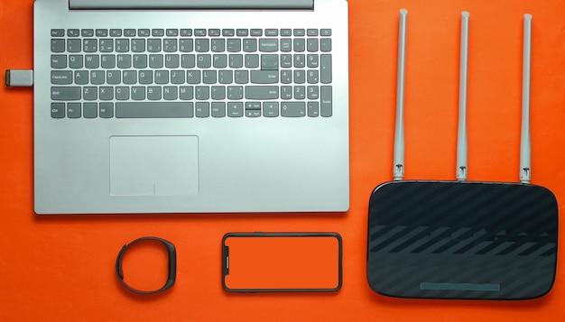 Ordenador portátil, enrutador wi-fi, teléfono inteligente, rastreador inteligente, sobre fondo naranja