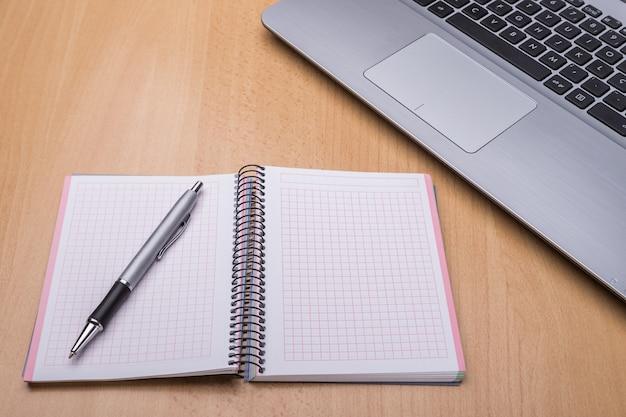 Ordenador portátil en el escritorio de la oficina. blocs de notas, primer plano.