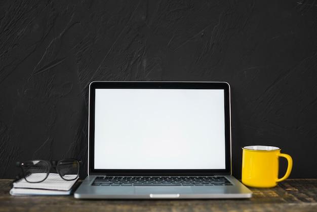 Ordenador portátil; espectáculo; taza de café amarillo y diario en mesa con pared texturada negra