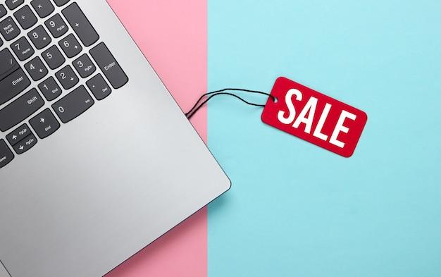 Ordenador portátil con una etiqueta de venta roja sobre rosa azul pastel. gran venta, descuentos, compras online.