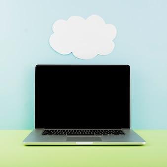 Ordenador portátil frente a la pared con papel de nubes