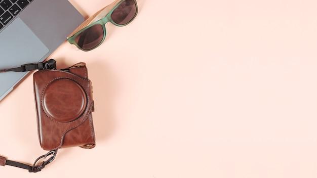 Ordenador portátil; gafas de sol y cámara en su funda sobre fondo de color liso.