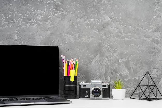 Ordenador portátil y herramientas de oficina en escritorio.