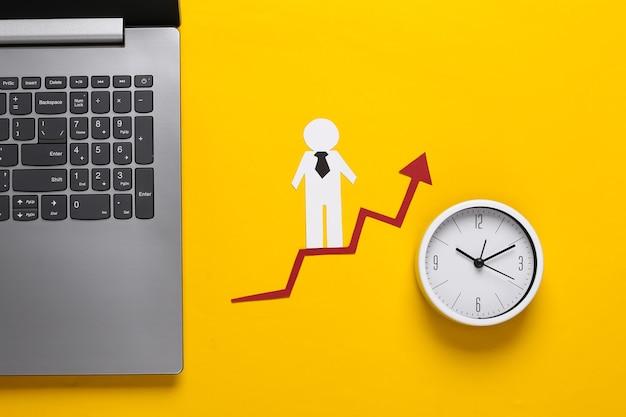 Ordenador portátil, hombre de negocios de papel en la flecha de crecimiento, reloj. amarillo. símbolo de éxito económico y social, escalera al progreso.