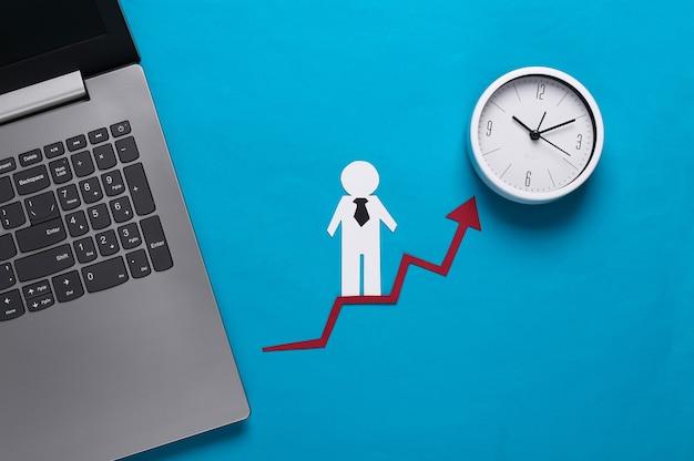 Ordenador portátil, hombre de negocios de papel en la flecha de crecimiento, reloj. azul. símbolo de éxito financiero y social, escalera al progreso