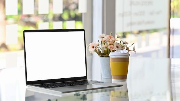 Ordenador portátil, llevar café y flores en la mesa