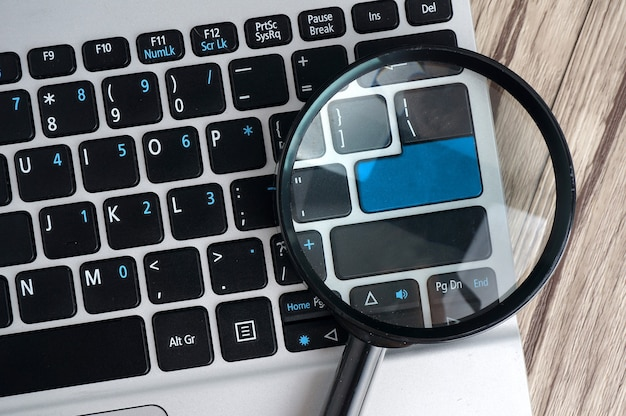Ordenador portátil con lupa, concepto de búsqueda