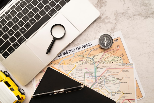 Ordenador portátil y mapas sobre fondo de mármol