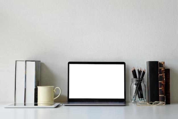 Ordenador portátil de la maqueta del espacio de trabajo de la oficina, libros, lápiz y taza de café en el escritorio de oficina.