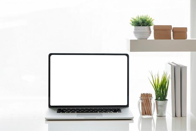 Ordenador portátil de la maqueta con la pantalla blanca y fuentes en la tabla blanca.