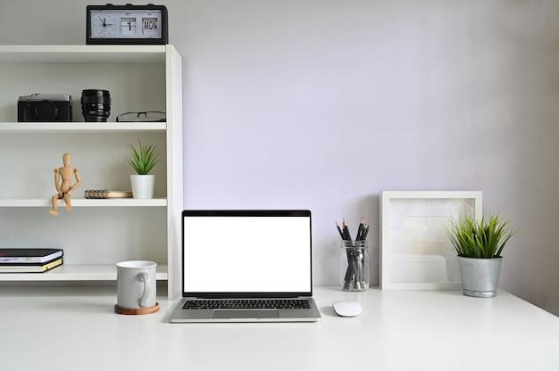 Ordenador portátil de la maqueta y taza de café en espacio de trabajo.