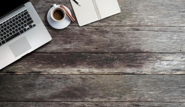 Ordenador portátil de la maqueta con la taza de café y la página en blanco del diario en la tabla de madera vieja.