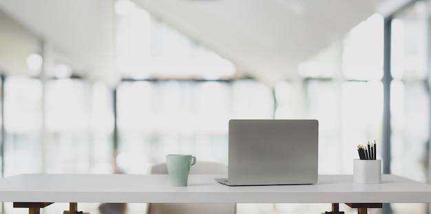 Ordenador portátil en mesa blanca y taza de café en la oficina moderna