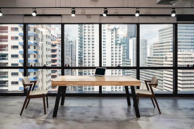 Ordenador portátil en la mesa de conferencias de madera con silla concepto de distanciamiento social en la oficina moderna reabrir