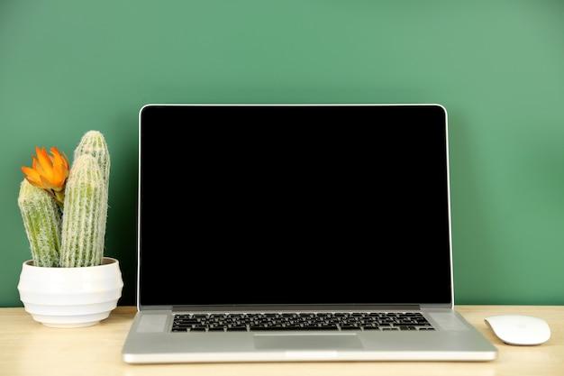 Ordenador portátil en la mesa en la pizarra verde