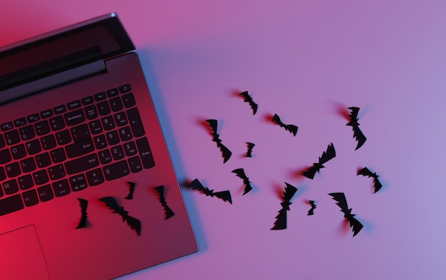 Ordenador portátil y murciélagos de corte de papel volador en luz rosa azul neón. tema de halloween