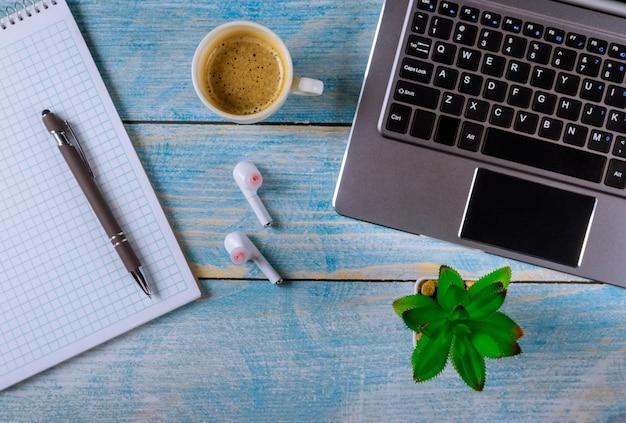 Ordenador portátil oficina cosas auriculares inalámbricos y taza de café bolígrafo vista superior tiro.