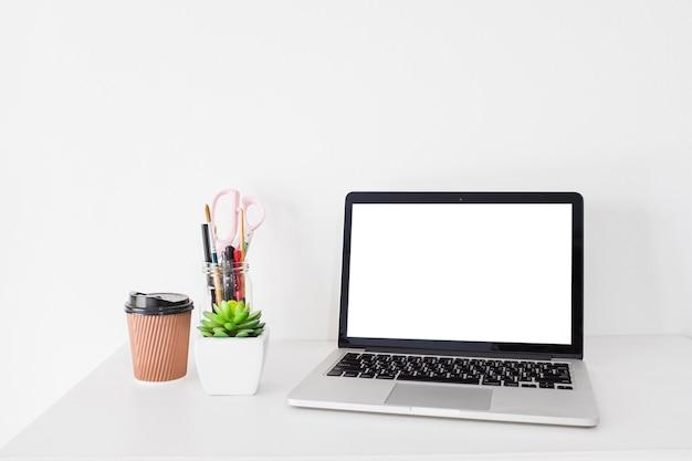 Ordenador portátil con pantalla blanca en blanco y taza de disposición en el escritorio