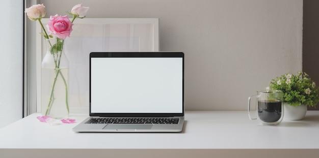 Ordenador portátil de pantalla en blanco abierto con marco de maqueta con jarrón de rosas y taza de café