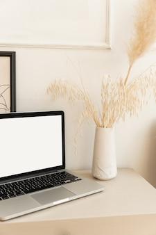 Ordenador portátil con pantalla en blanco beige pastel en mesa con decoraciones boho. ramo de hierba de pampas de cañas esponjosas.