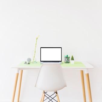 Ordenador portátil con pantalla en blanco en blanco en el escritorio frente a la pared