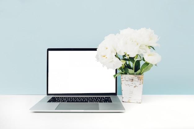 Ordenador portátil con pantalla en blanco blanco y flores en florero sobre la mesa en azul. bosquejo