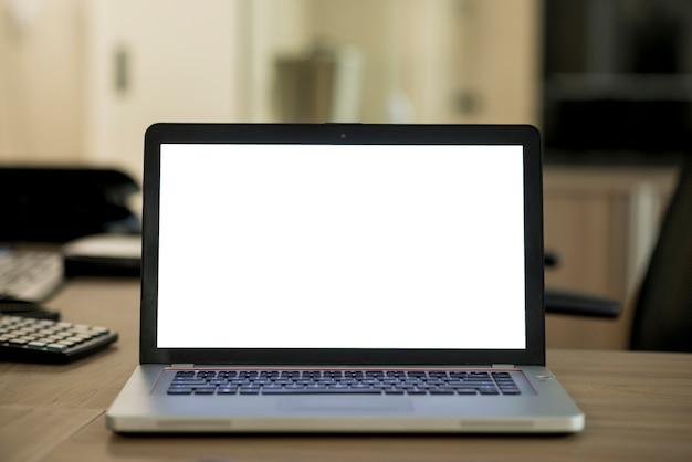 Ordenador portátil con pantalla en blanco en blanco sobre el escritorio de madera