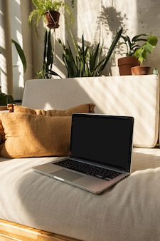 Ordenador portátil con pantalla en blanco en un cómodo sofá en las cálidas sombras de la luz del sol. diseño interior minimalista de estilo boho.