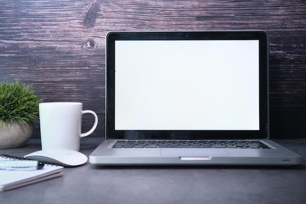 Ordenador portátil con pantalla en blanco en el escritorio de oficina.