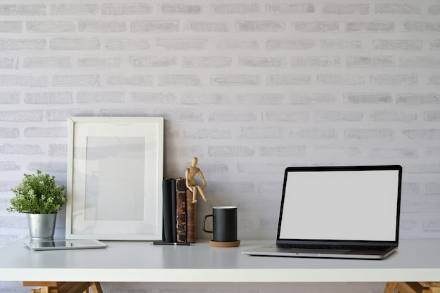 Ordenador portátil de la pantalla en blanco del espacio de trabajo y cartel de maqueta en la mesa de oficina de escritorio blanco