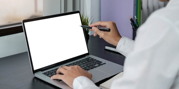 Ordenador portátil de pantalla en blanco y fondo del espacio de trabajo del cartel en la oficina moderna