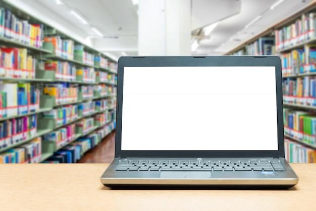 Ordenador portátil con pantalla en blanco en la mesa con biblioteca borrosa en libraly
