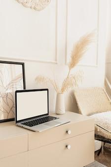 Ordenador portátil con pantalla en blanco en la mesa con decoraciones boho