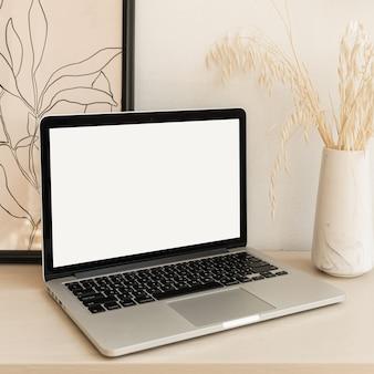 Ordenador portátil con pantalla en blanco en la mesa con decoraciones boho.