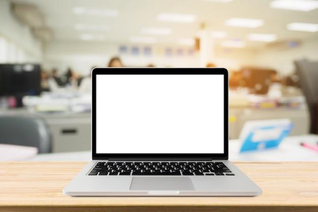Ordenador portátil con pantalla en blanco en la mesa de escritorio con desenfoque de fondo interior de la oficina
