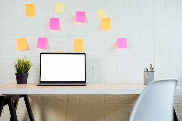 Ordenador portátil de la pantalla en blanco en la mesa de madera en la oficina de la habitación.