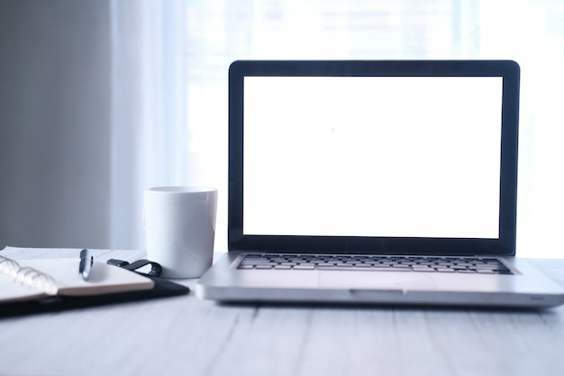 Ordenador portátil con pantalla en blanco con taza de café con leche en el escritorio de oficina.