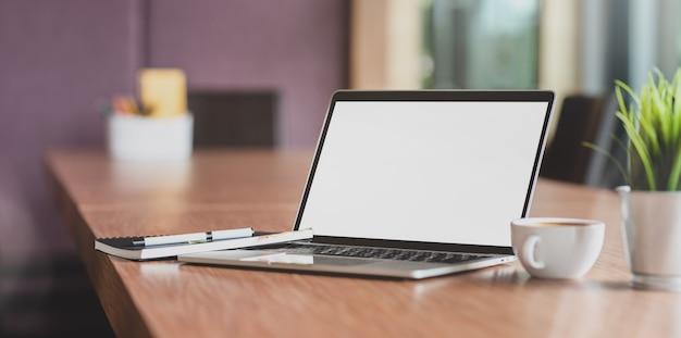 Ordenador portátil con pantalla en blanco y una taza de café en la moderna sala de reuniones