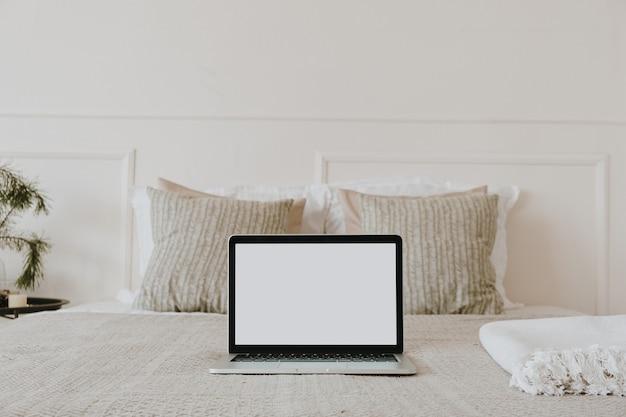Ordenador portátil con pantalla de espacio de copia en blanco en la cama con cuadros, almohadas contra la pared blanca. composición estética de la mañana.