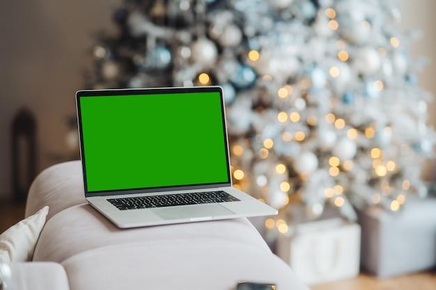 Ordenador portátil con pantalla verde chromakey cerca de tema navideño de decoraciones de año nuevo